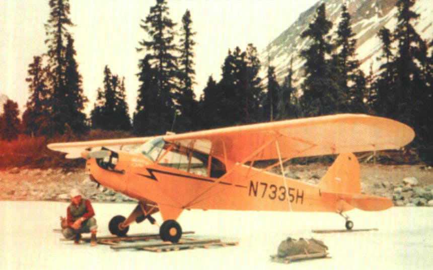 Richard Proenneke crouched next to his Yellow Monoplane in Alaskan Forest