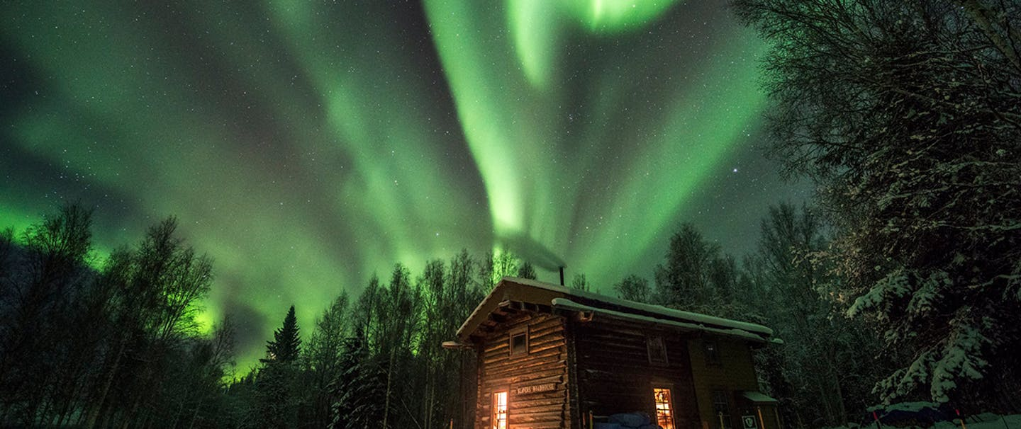 snow covered lit cabin in forest with green northern lights above