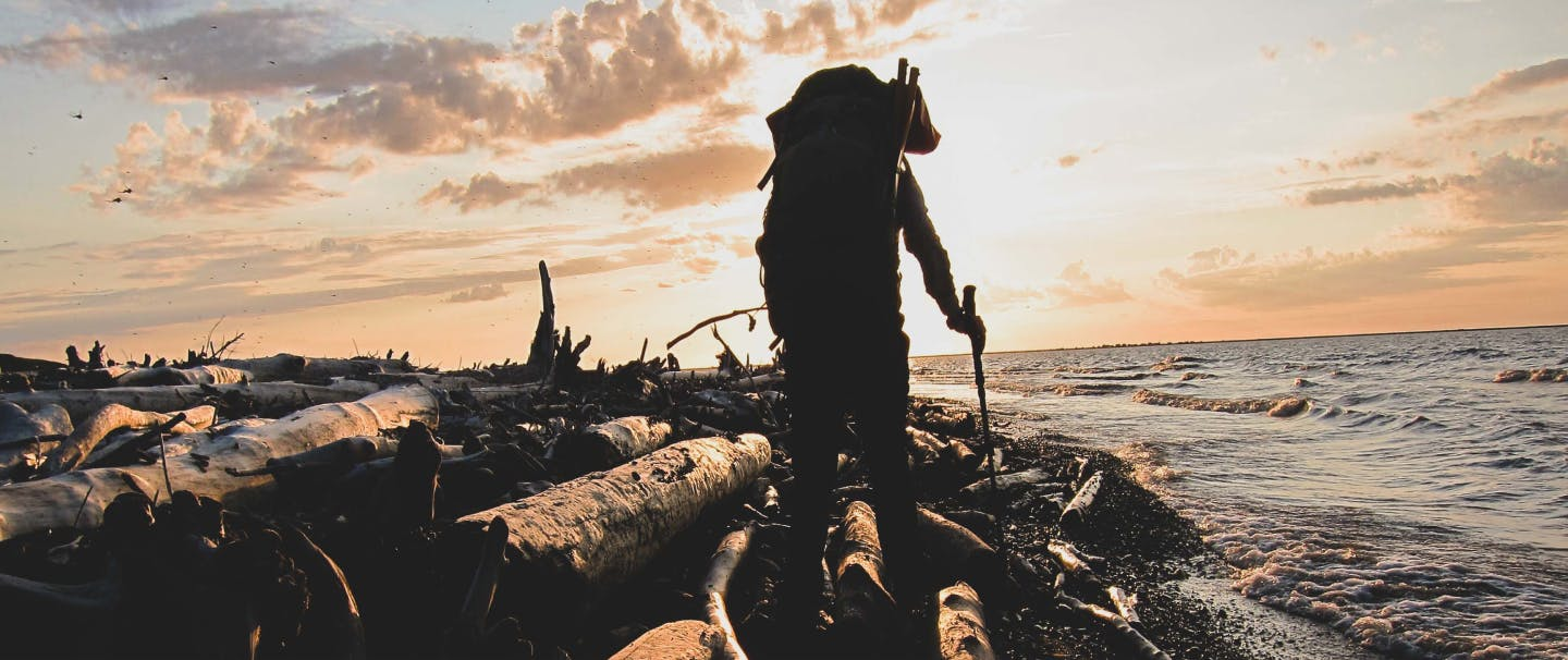 Silhouette of man with walking pole and backpacking backpack walking along beach with downed logs