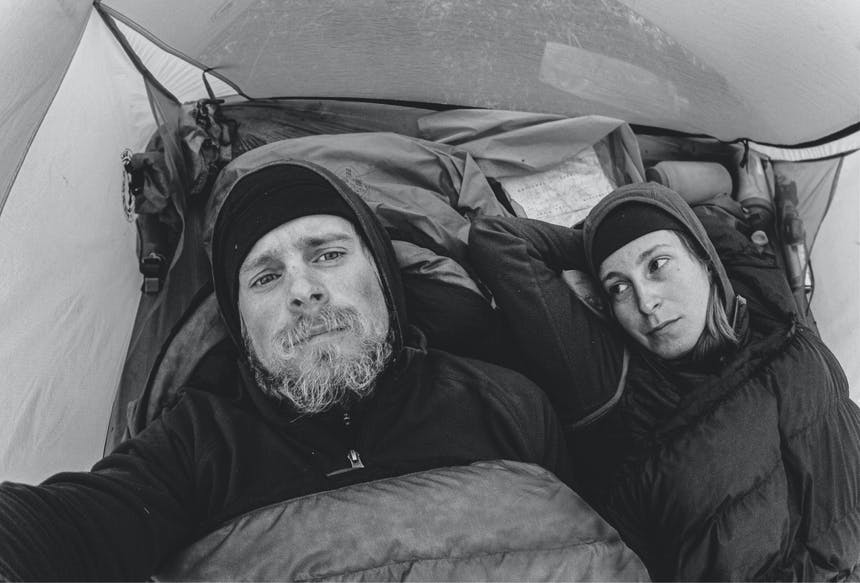 Black and White Man and woman in cold weather gear in tent in sleeping bags