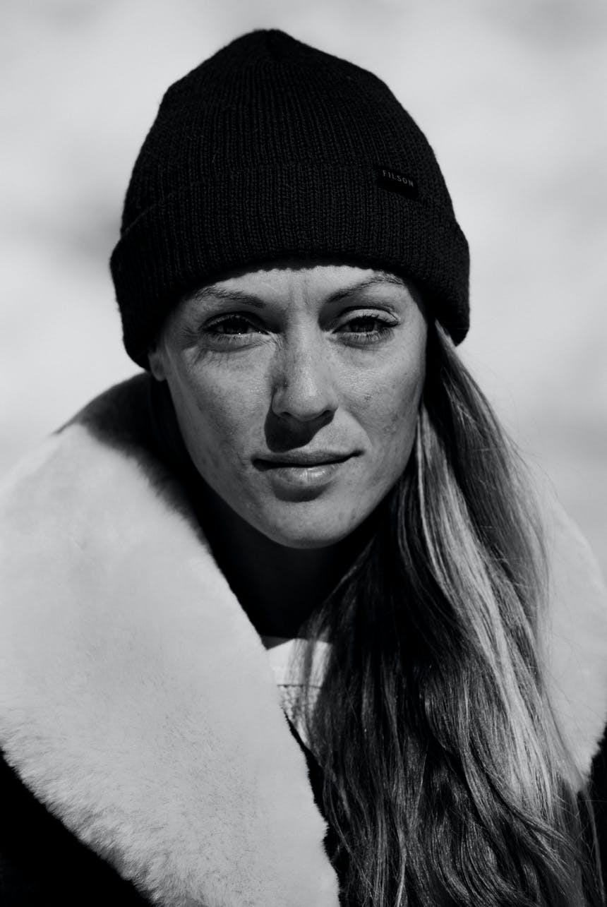 portrait of woman with long blonde hair in a fur lined coat with black beanie