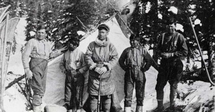 old black and white photo of men standing in front of tent in snowy forest