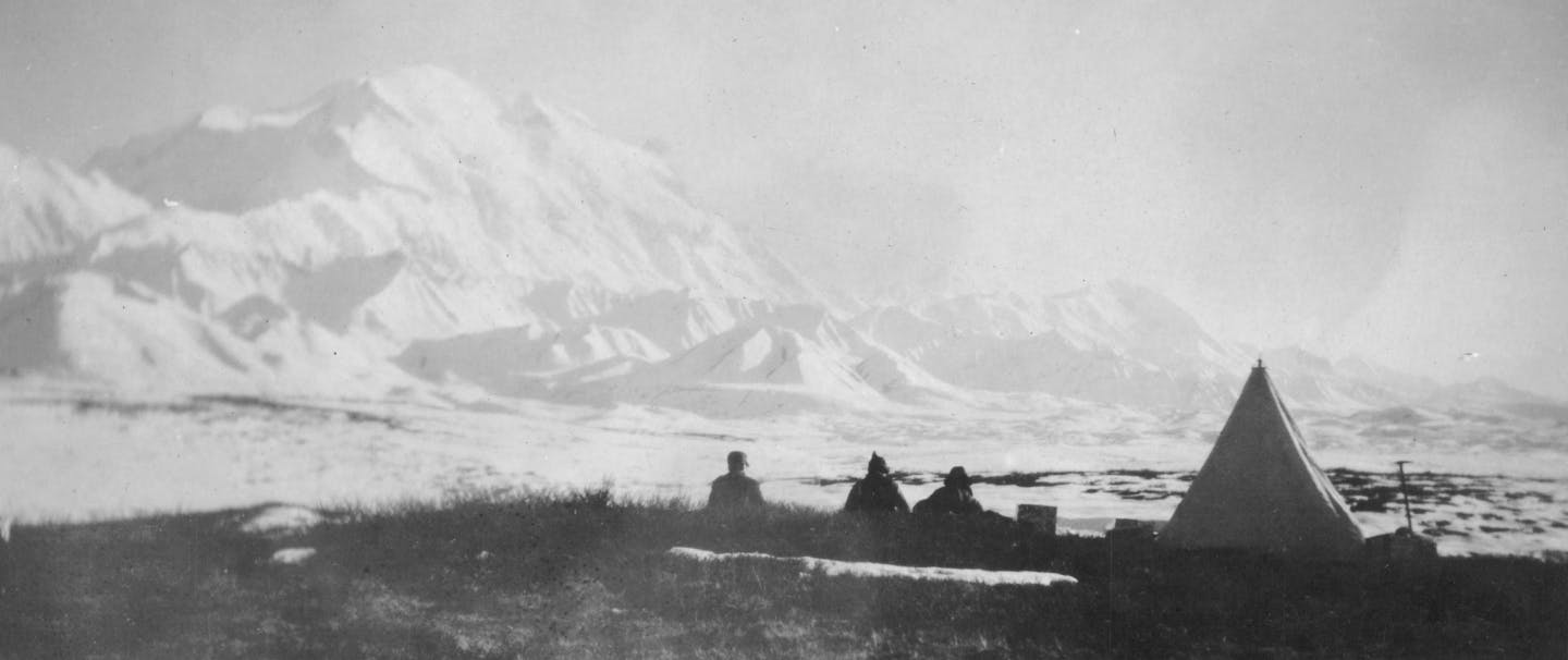 old black and white image of walter harper siting looking out at Denali