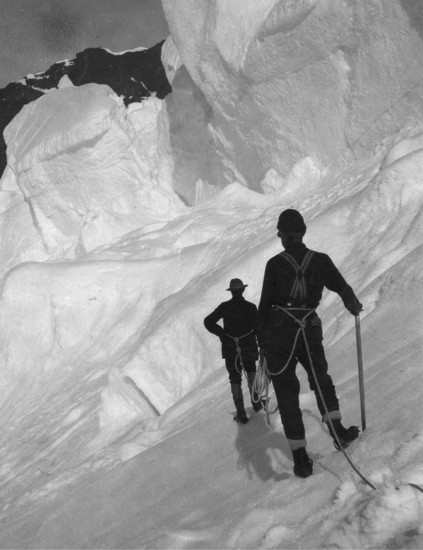 walter harper man on safety line look at large snowy glacier-like cliff in front of them
