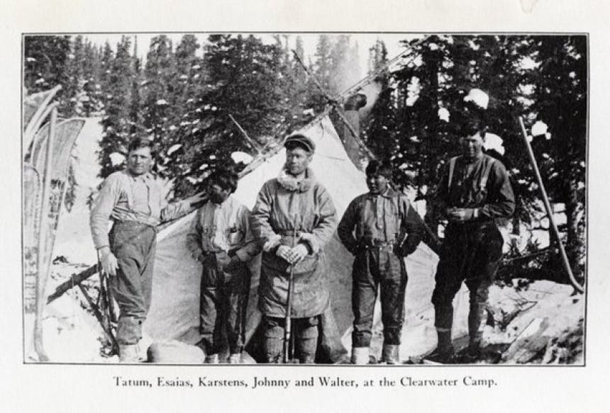 old black and white photo of men standing in front of tent in snowy forest names beneath: Tatum, Esaias, Karstens, Johnny and Walter, at the Clearwater Camp