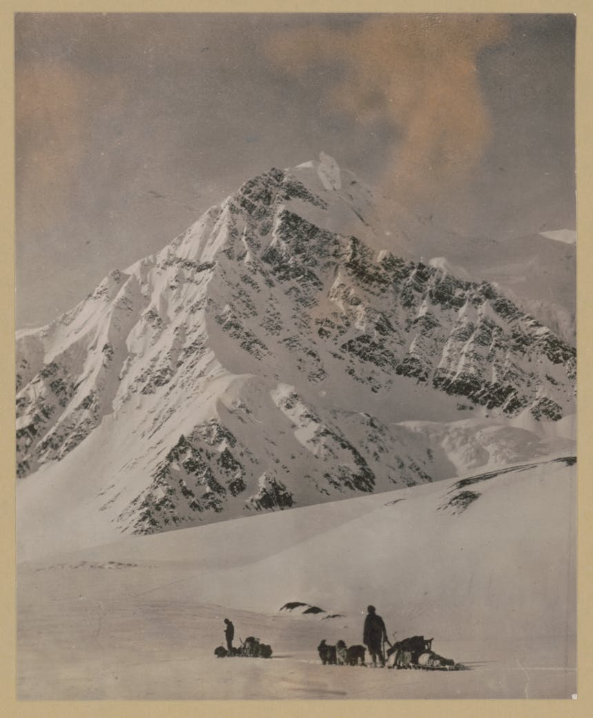 black and white image of sled dog teams in front of imposing snowy peak