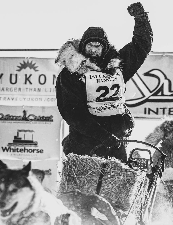 Musher in black coat raises fist while on sled dog sled