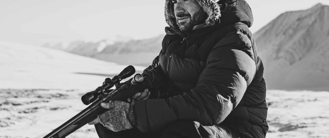 man in fur lined ushanka hat and black parka sitting in a snowy arctic plain holding a rifle with mountains in the background