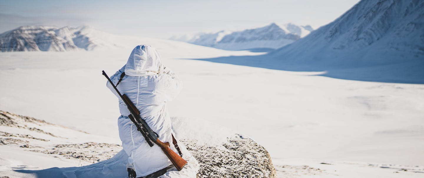 person in white parka looking out over a vast snowy plain with mountains with rifle over his back