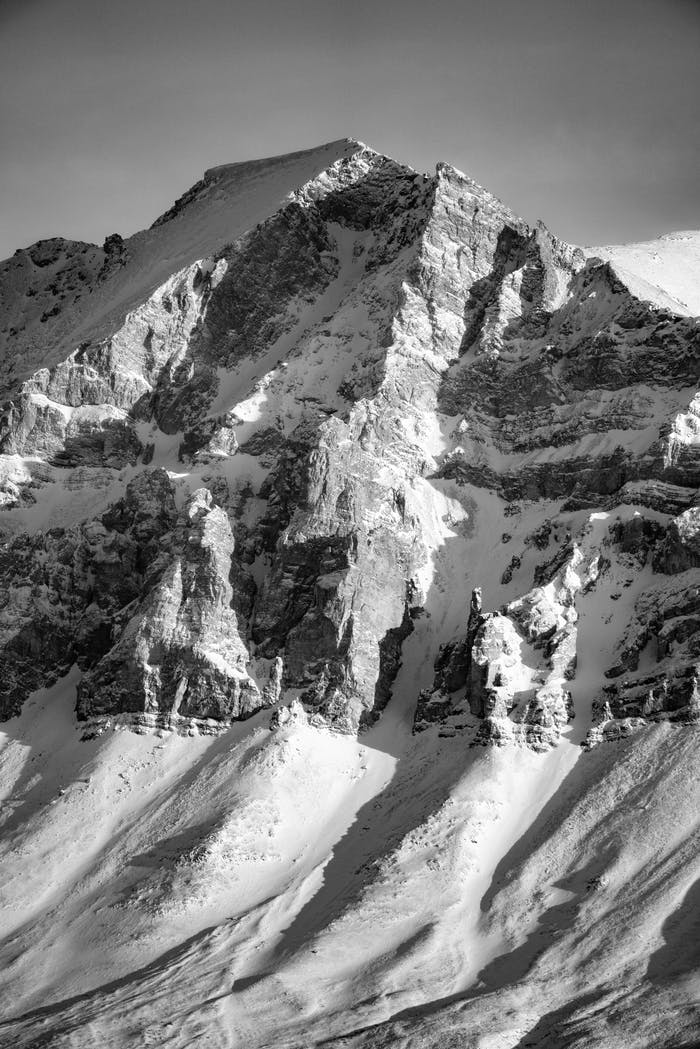 black and white image of an imposing snow covered rocky mountain peak