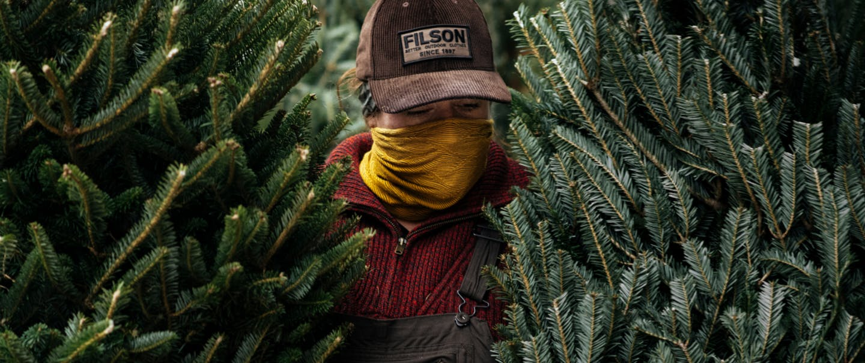 emily mullen in brown filson hat standing between two pine trees