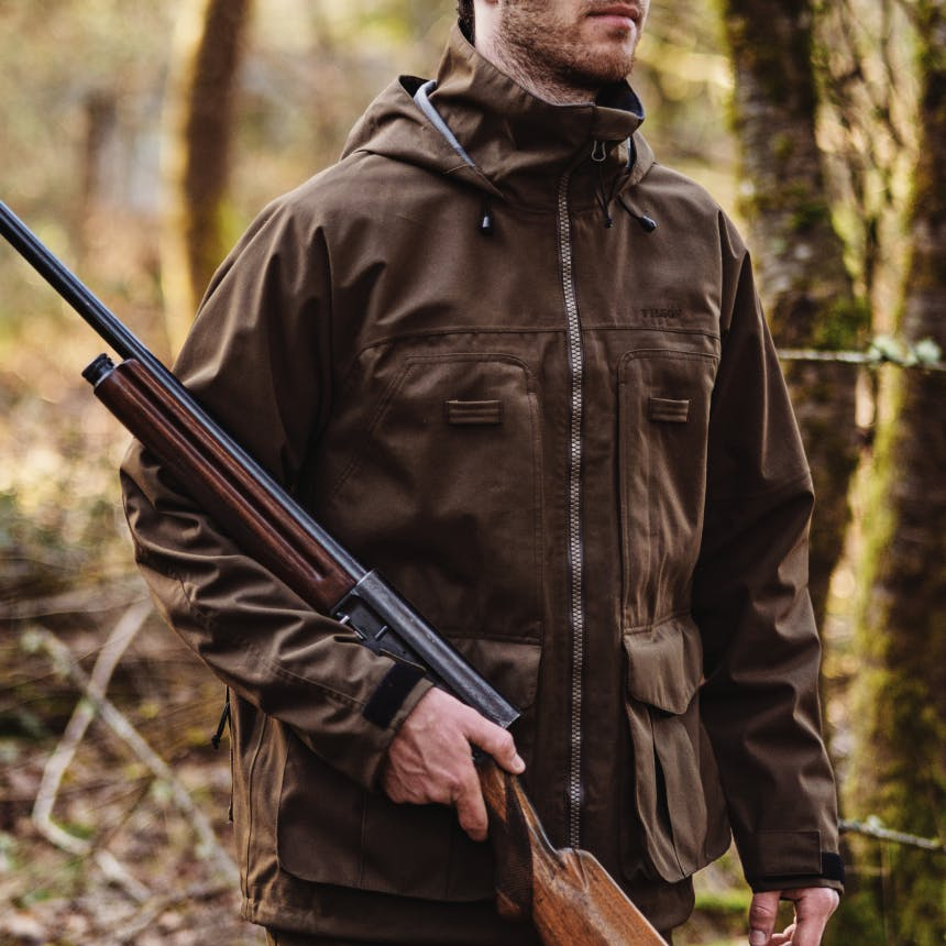 man in brown filson coat holding a shotgun in a forest
