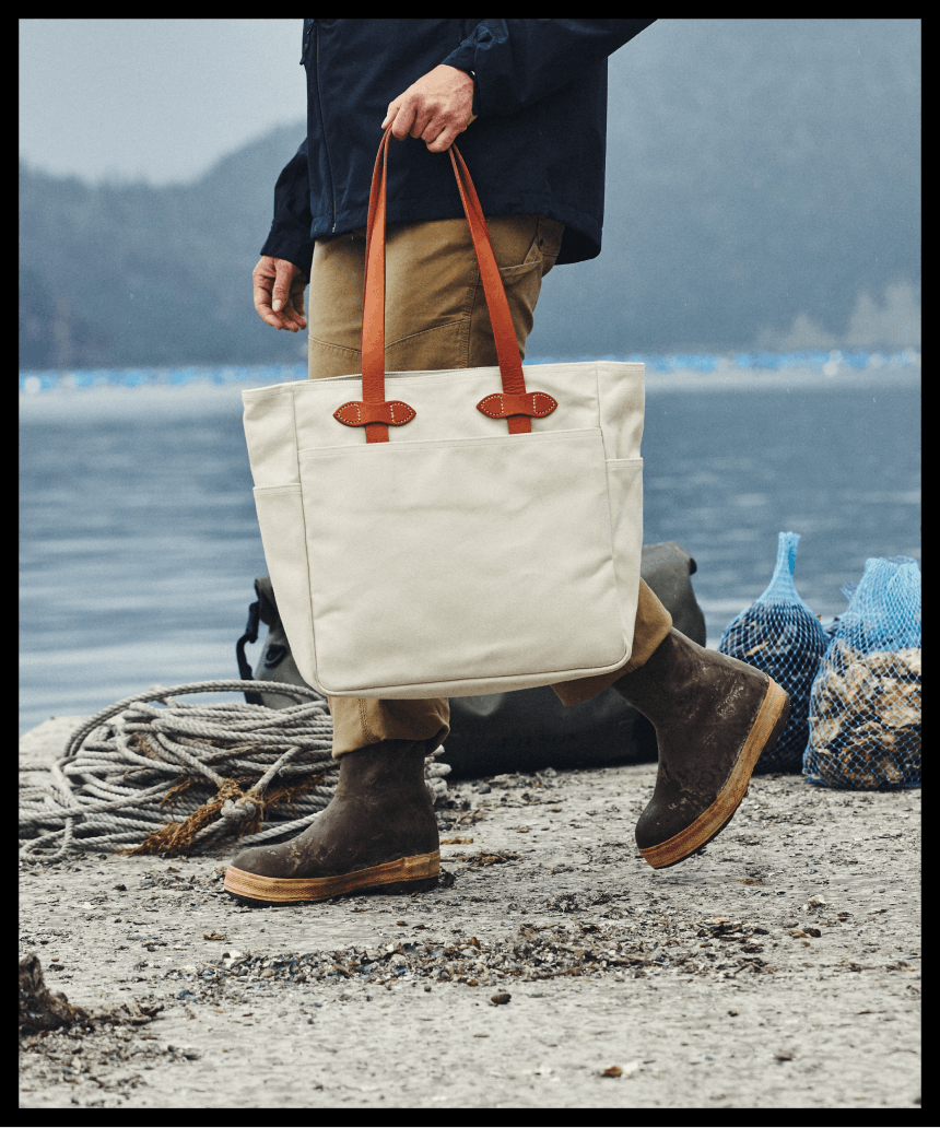 person walking along a beach holding a white tote bag with burnt orange leather handles