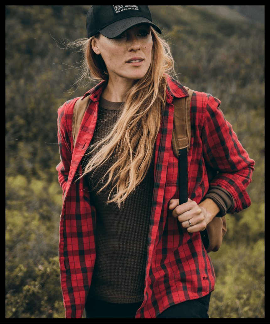 woman in red plaid flannel with a backpack on standing in a field of low lying brush