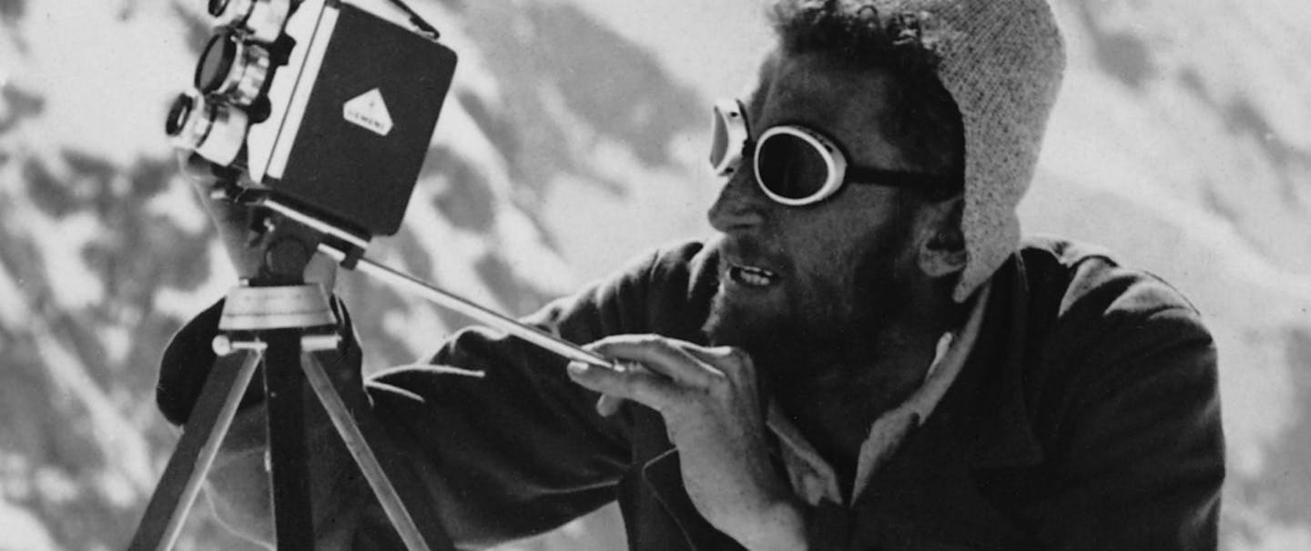 man in glacier goggles looking through an old fashioned video camera