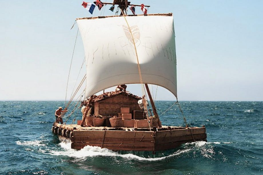 wooden raft at sea with single sail being steered by a man