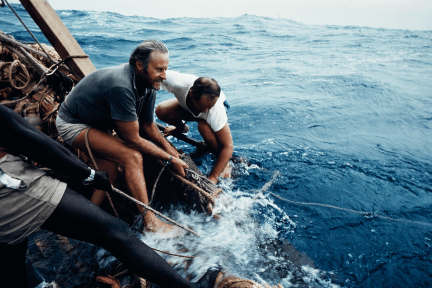 three men pulling in a line while on a raft