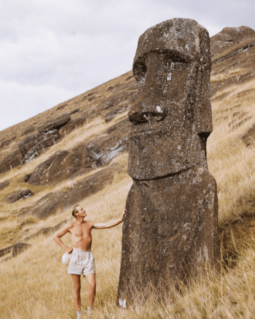 man in white shorts standing next to a moa statue on easter island