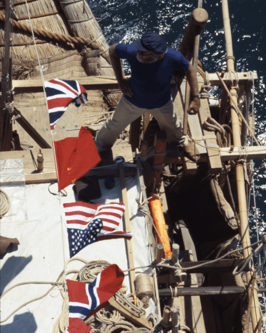 man in blue shirt standing on the deck of a boat under a number of flags hanging on a line