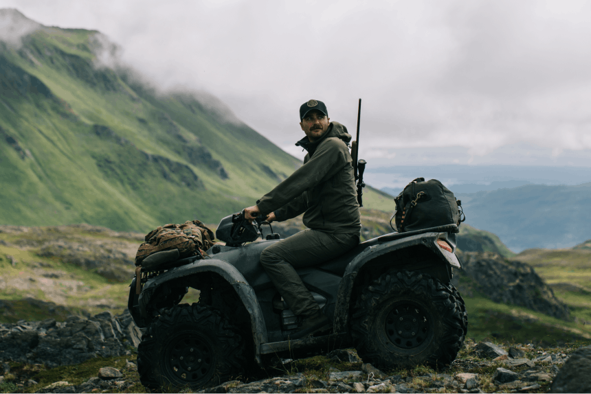 person on atv with rifle on his back in lush green mountain pass