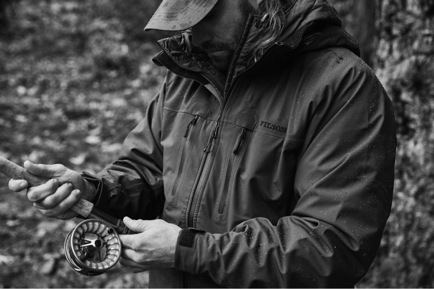 person in filson rain coat inspecting a fly fishing rod