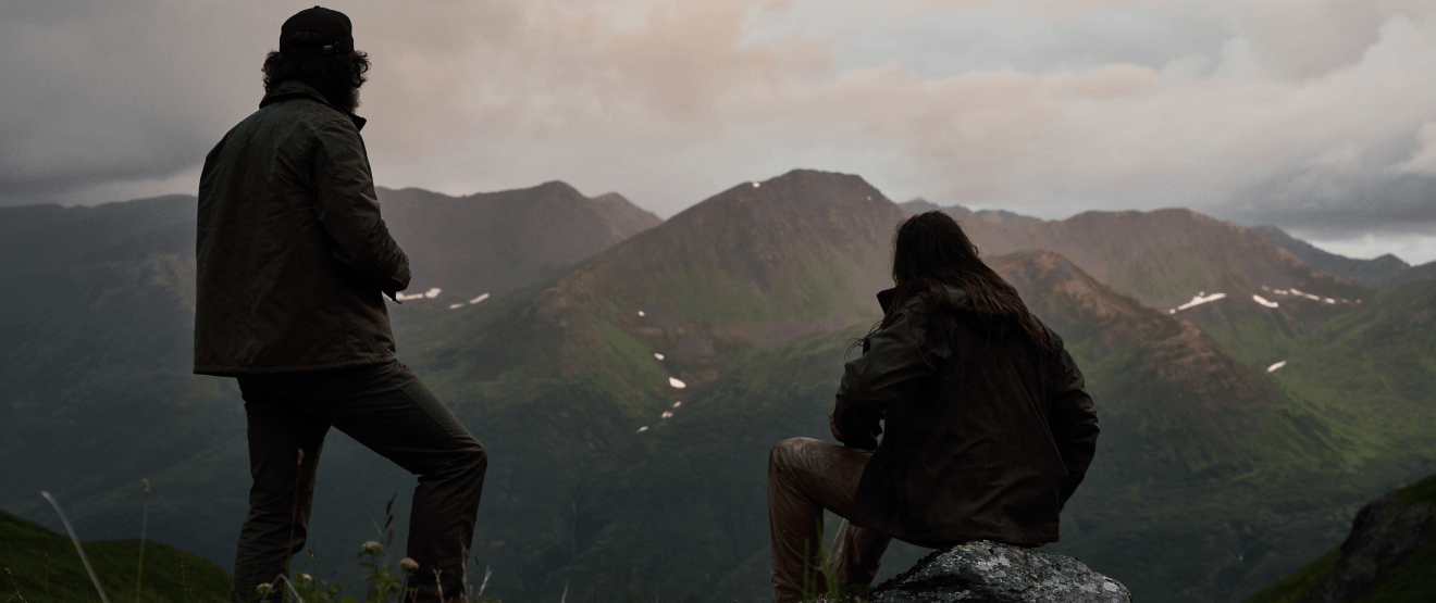 two people sitting on the ridge of a mountain looking out at distant peaks