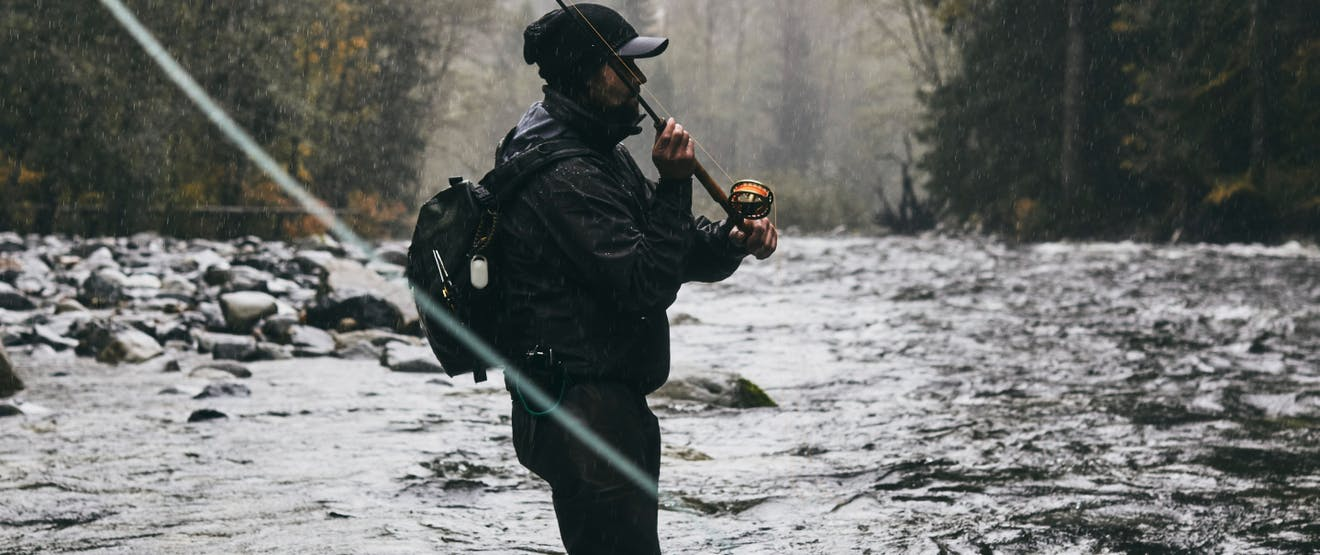 person in black rain coat and backpack casting a fly fishing rod in a river
