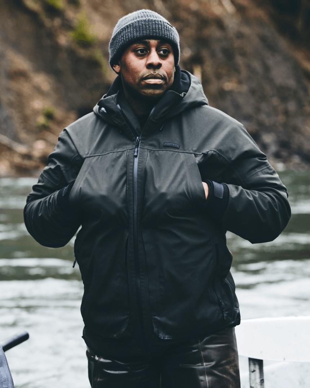 man in dark rain coat standing in water in a river