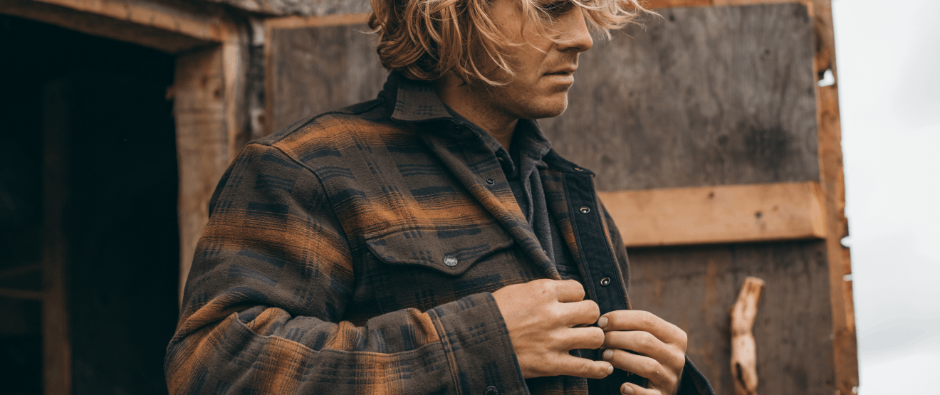 person in two toned brown button up plaid shirt standing in front of a wooden barn door