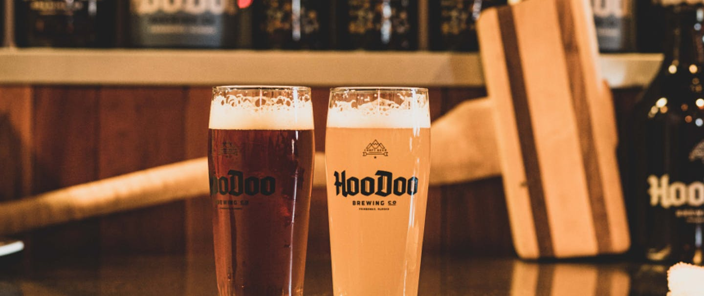 two pint glasses of hoodoo beer on a stainless steel counter with growlers of different sizes behind them
