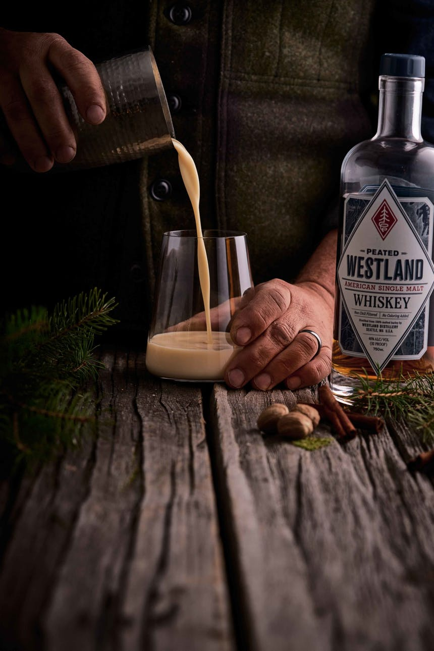 hands pouring a cocktail from a metal shaker into a cocktail glass on a wooden table next to a westland whiskey bottle