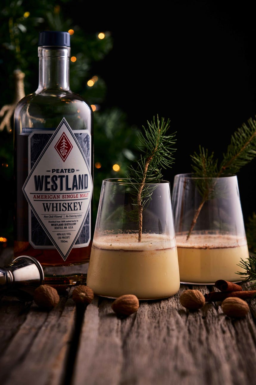 westland whiskey cocktail in two glasses next to a bottle of westland whiskey on a wooden table
