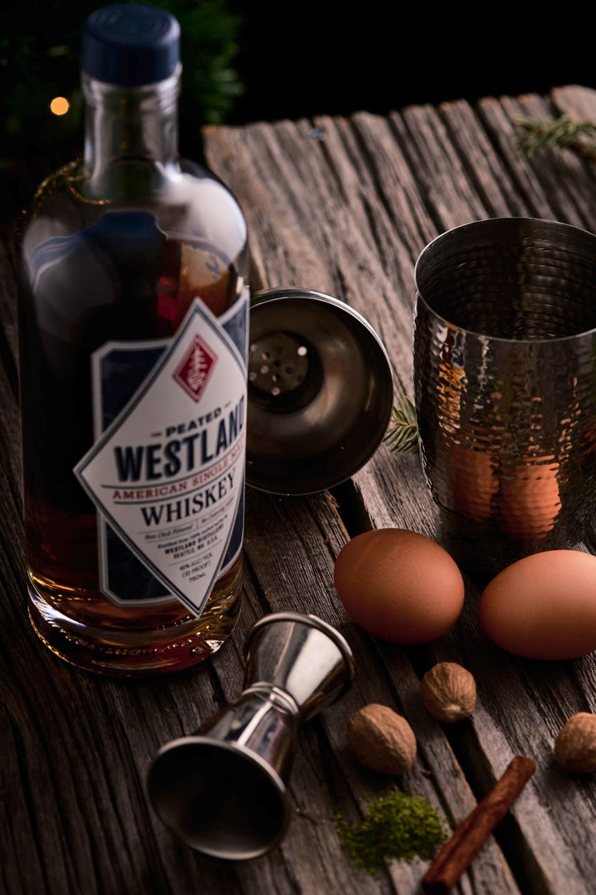 bottle of westland whiskey cocktail shaker, jigger, two eggs, on a wooden table
