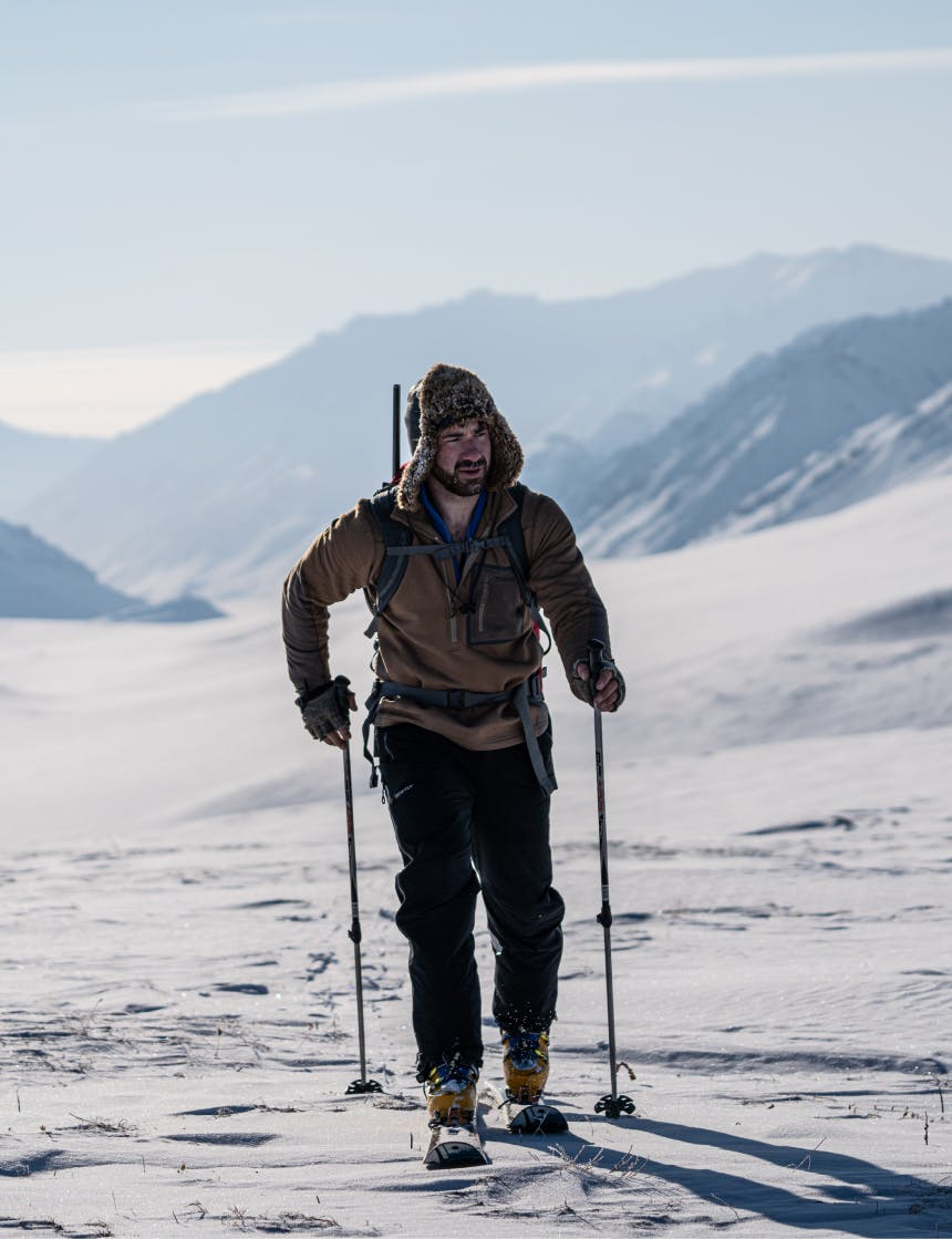 person in skis and fur lined ushanka hat traverses a snowy plain in arctic mountains