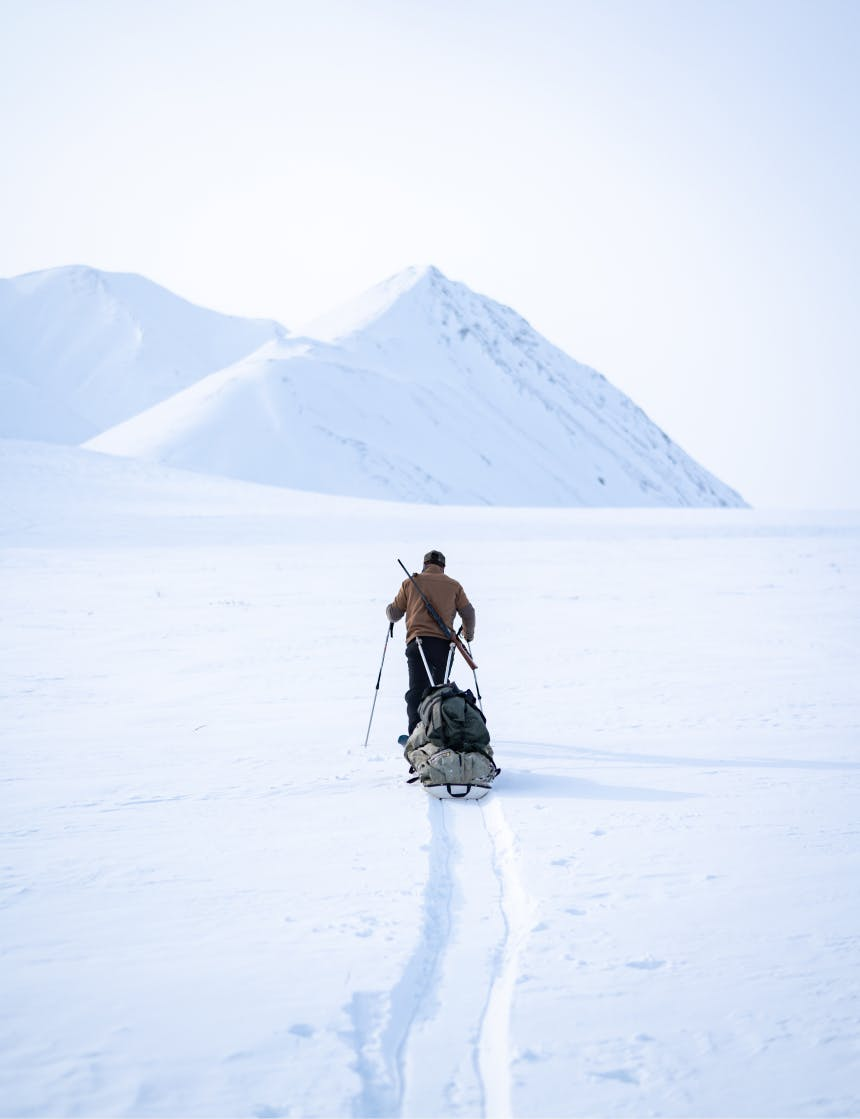 person on skis pulls a sled behind them toward a snow covered peak