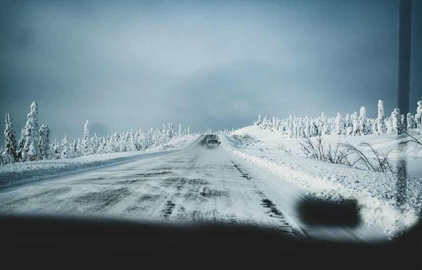 truck driving down a snowy road in a high tundra plain