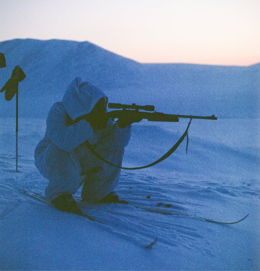 person on skis crouched aiming a rifle in a snowy plain at sunset