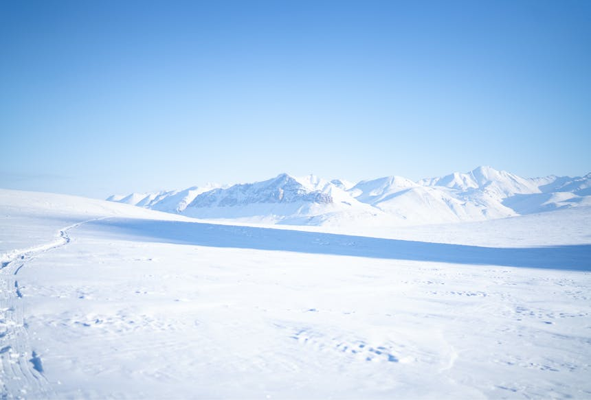 vast snowy plain with mountains in the distance