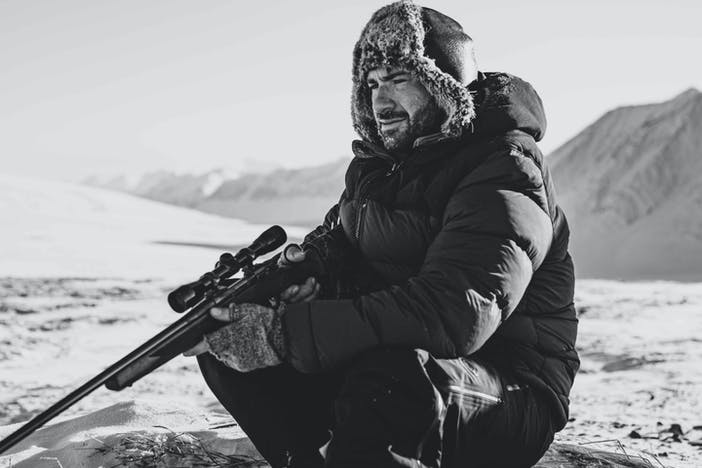 person in a fur hat with ear flaps, black parka, holding a rifle sitting in a snowy field with mountains in the background