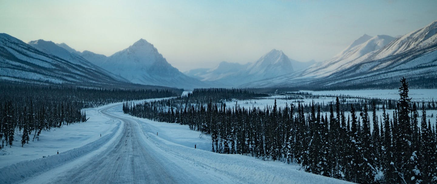 snowy highway stretches toward the distant snow covered peaks in the distance