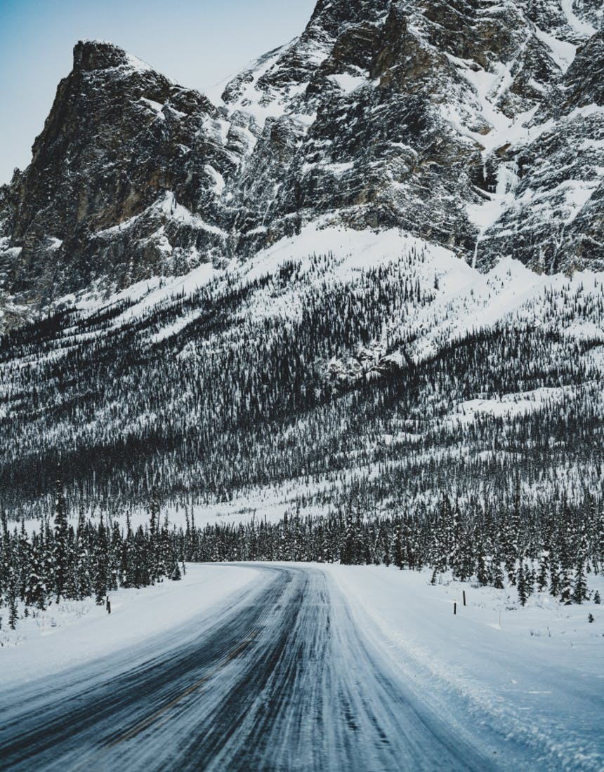 frozen road trailing away toward a craggy snow covered mountain peak