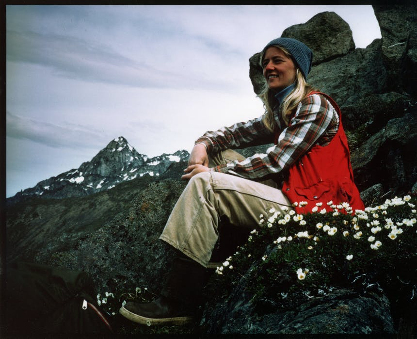 woman in red vest, white pants, and orange and white plaid shirt sitting on a rocky mountain escarpment next to some small white flowers