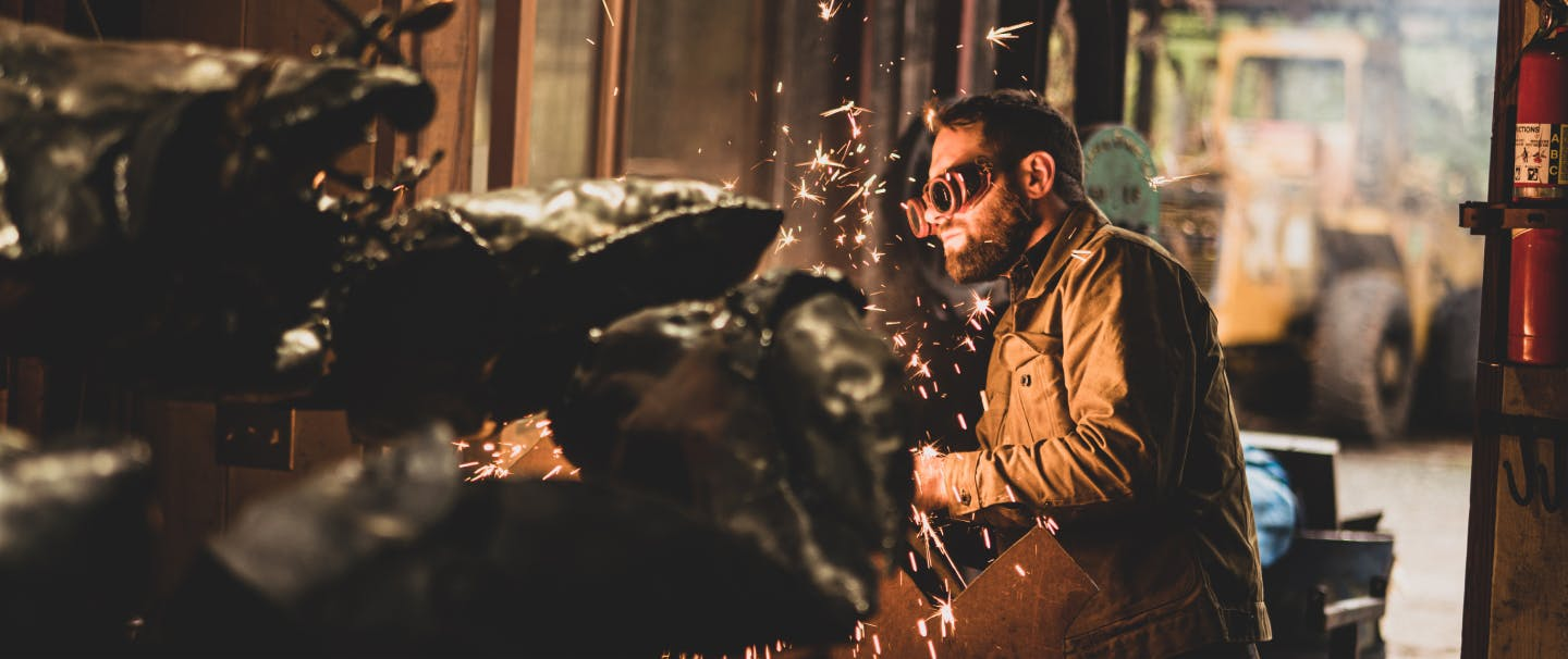 person in goggles making sparks while working on a metal sculpture in a workshop