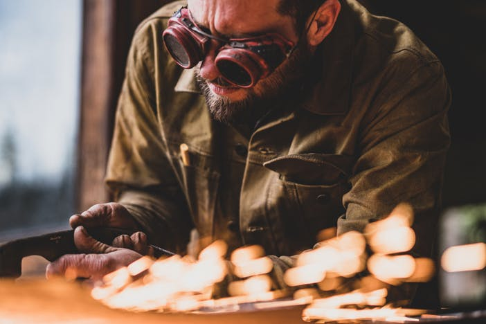 person in goggles and tin cloth jacket working on a piece of metal producing lots of sparks