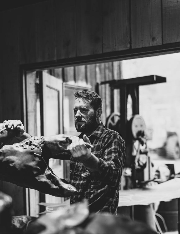 man touching a metal sculpture in a workshop