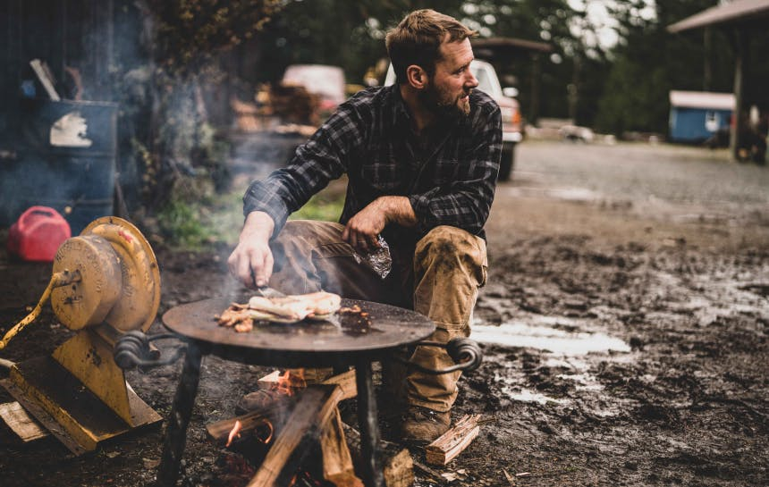 person tending to fish cooking on a metal table over a wood fire in a muddy plot