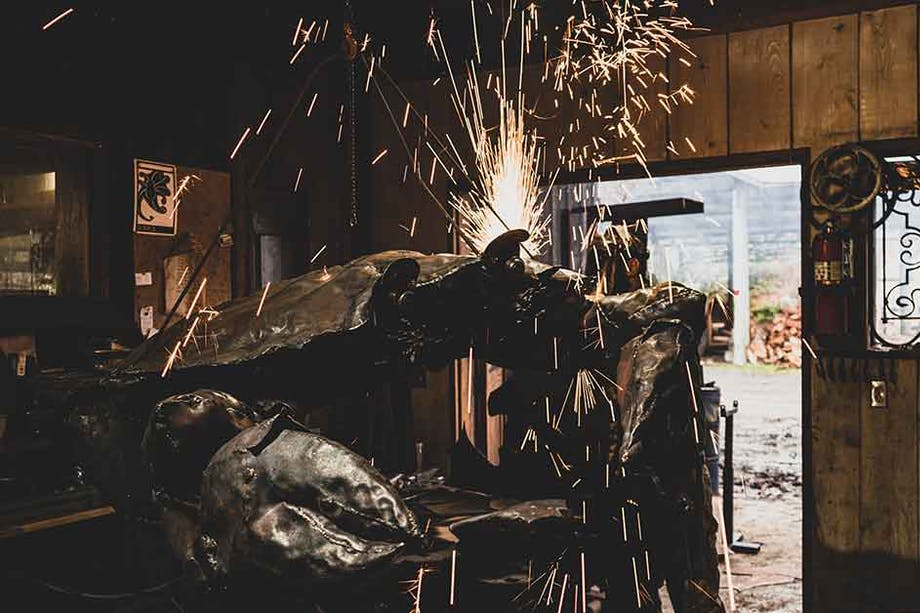 person in a workshop using an angle grinder producing large amounts of sparks on a piece of metal