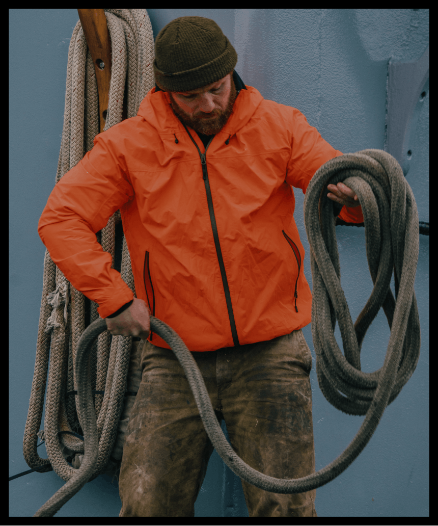 person in orange jacket and olive beanie coiling thick rope on a boat