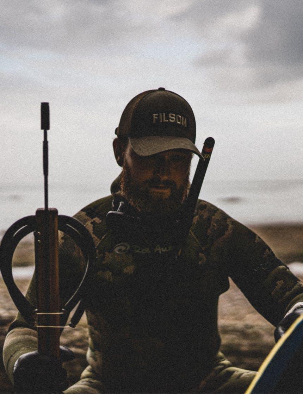 person in brown filson hat sitting on beach in wetsuit holding a harpoon gun