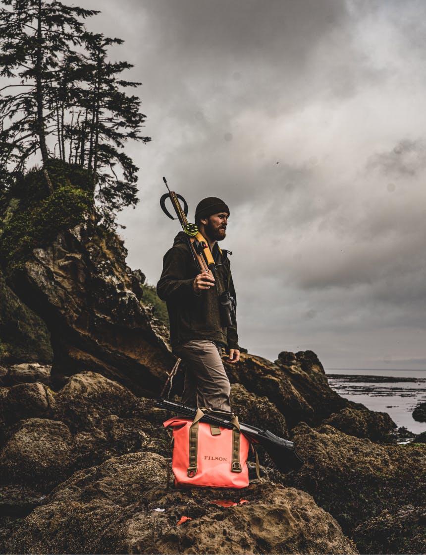 man in black beanie standing on beach holding a harpoon gun over his shoulder next to an orange dry filson bag